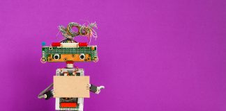 Robot with a cardboard card mockup. Creative design robotic toy holding a blank empty paper poster, purple wall background. copy space for text and design elements